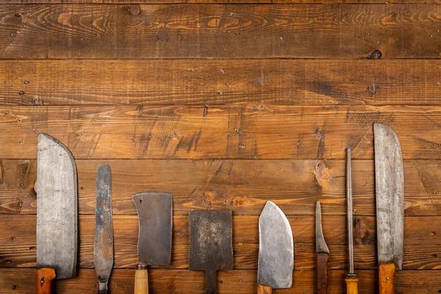 Alte küchenmesser im hölzernen hintergrund