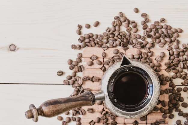 Alte kupferkaffeekanne und kaffeebohnen, draufsicht