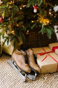 Alte lederschlittschuhe unter weihnachtsbaum mit geschenkboxen