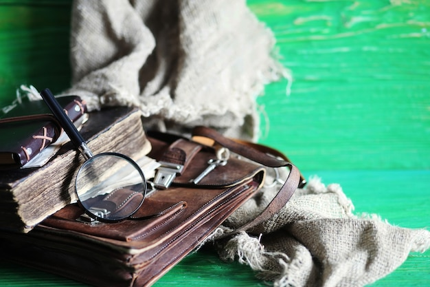 Alte ledertasche mit lupe auf braunem holztischhintergrund des reisenden mit kopienraum.