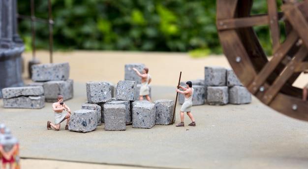 Alte leute arbeiten mit stein, miniaturszene im freien, europa. mini figuren mit hoher entkalkung von objekten, realistisches diorama, spielzeugmodell