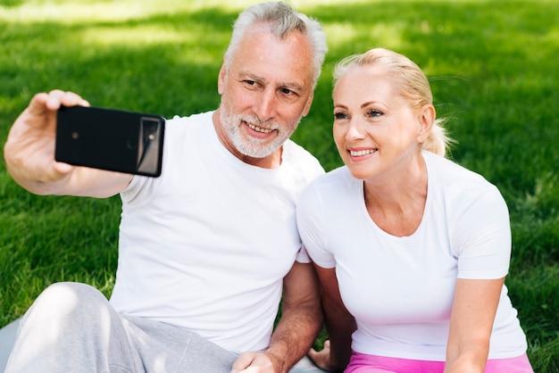 Alte leute des mittleren schusses, die draußen selfies nehmen