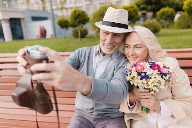 Alte leute verabreden sich und machen selfie auf alter filmkamera.