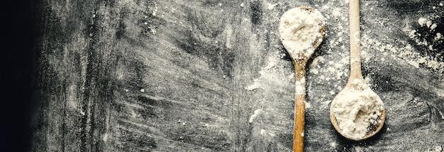 Alte löffel auf dunkler tabelle mit mehl