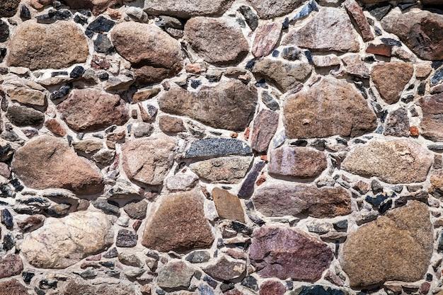 Alte mauer aus großen steinen und zerbrochenen ziegeln. weinlanger rauer blockoberflächenhintergrund