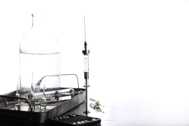 Alte medizinische retro-metallspritze und zubehör auf dem tisch