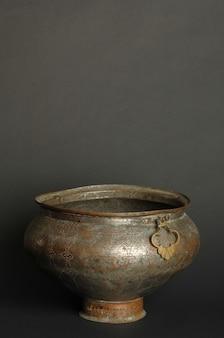 Alte metallschüssel auf dunklem hintergrund. antikes bronzegeschirr