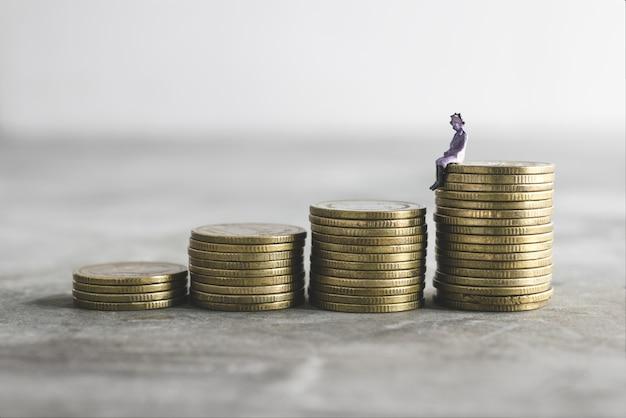 Alte miniaturdame auf das geld sparen geldkonzept.