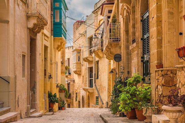 Alte mittelalterliche straße mit gelben gebäuden, schönen balkonen und blumentöpfen in birgu, valletta, malta