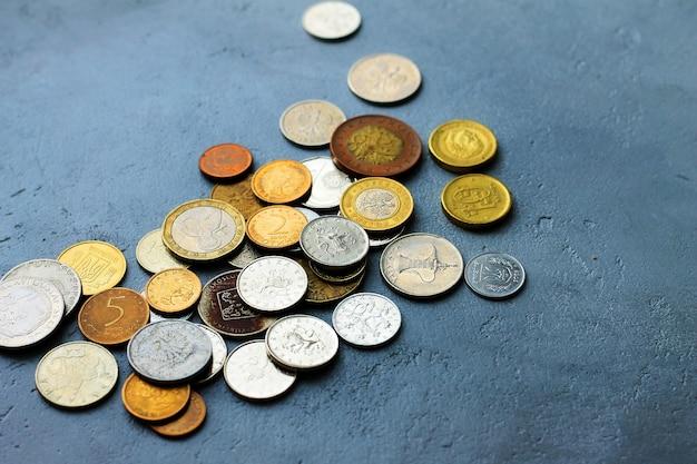 Alte münzen von verschiedenen ländern auf einem grauen konkreten hintergrund.