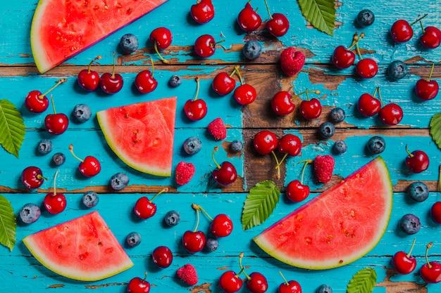 Alte oberfläche mit heidelbeeren, kirschen und wassermelonen portionen