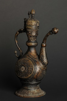 Alte orientalische metallteekanne auf dunklem hintergrund. antikes bronzegeschirr