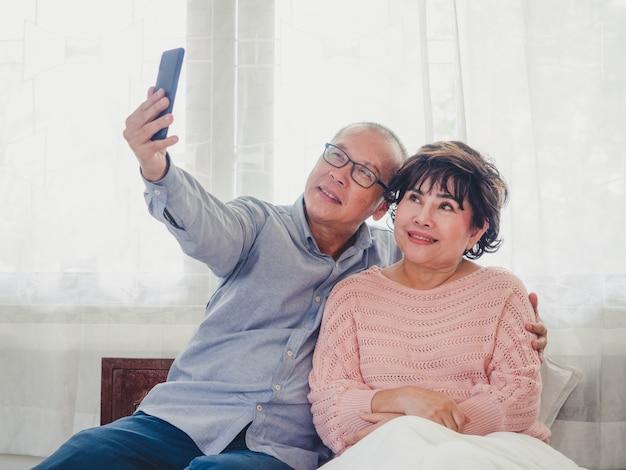 Aufpassendes fernsehen der asiatischen älteren paare im
