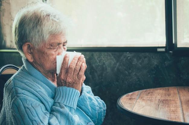 Alte person, die bedeckungsmund mit einem gewebe auf einem hausinnenraum husten lässt. sie hat grippe, allergiesymptome, akute bronchitis, lungeninfektionen oder lungenentzündung.