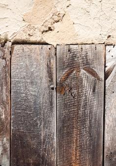 Alte pfeilerwand mit gebrochener oberfläche und alten hölzernen brettern