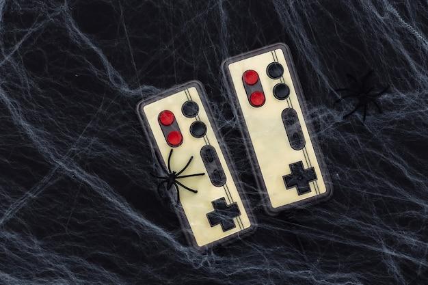 Alte retro-gamepads auf einem schwarzen mit spinnweben und spinnen. halloween-thema. spinnenphobie