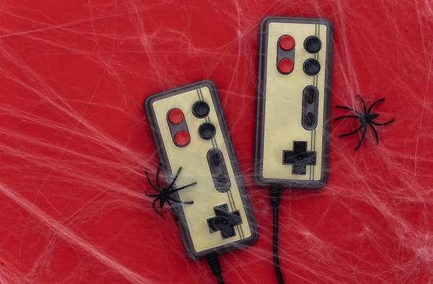 Alte retro-gamepads auf rot mit spinnweben und spinnen. halloween-thema. spinnenphobie