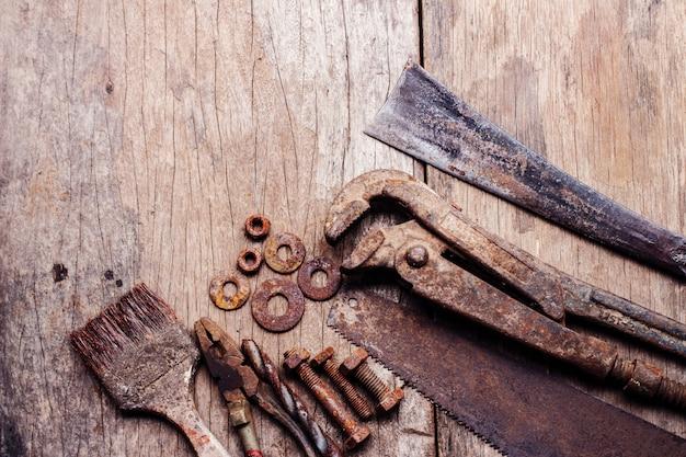 Alte rostige hilfsmittel auf altem hölzernem hintergrund. altes foto