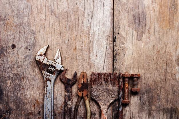 Alte rostige hilfsmittel auf altem hölzernem hintergrund