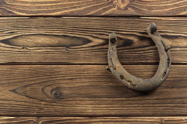 Alte rostige hufeisen auf hölzernem brett