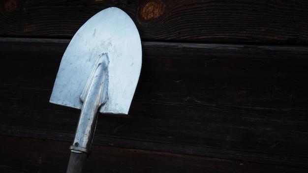 Alte rostige schaufelstütze gegen alte hölzerne wand, hölzerne beschaffenheit