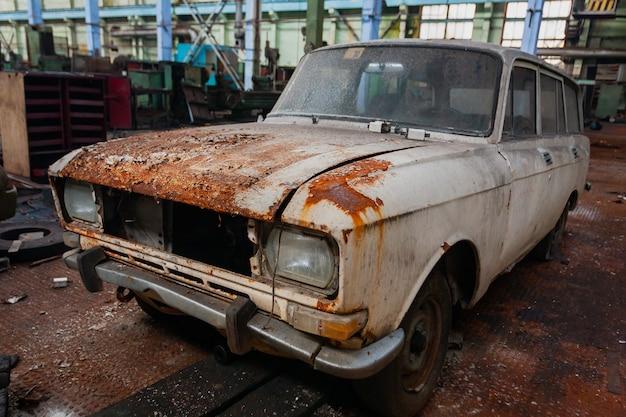Alte rostige sowjetische auto-vorderansicht auf dem gebiet der werkstatt einer verlassenen alten industrieanlage.