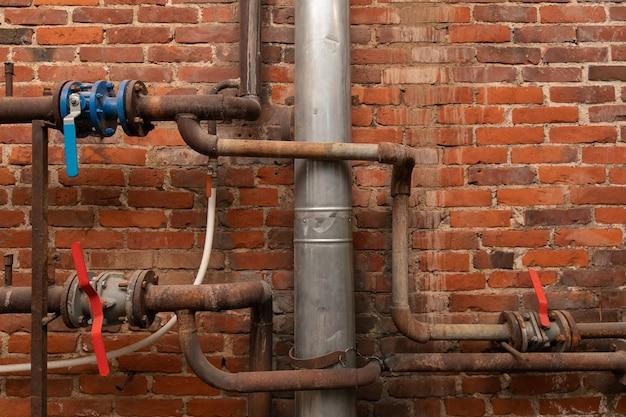 Alte rostige wasserrohre mit ventilen in einem industriegebäude gegenüber einer backsteinmauer.