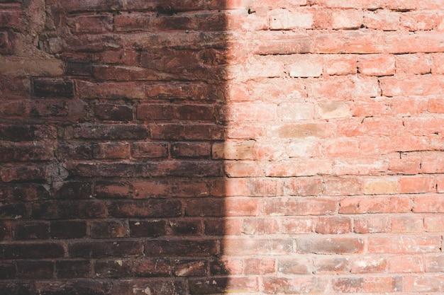 Alte rote backsteinmauer mit schattenhintergrund