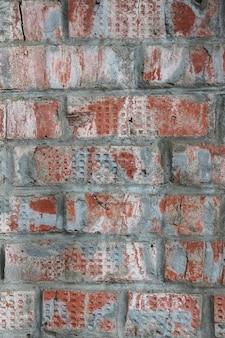 Alte rote backsteinmauer mit strukturiertem hintergrund der farbe und der risse