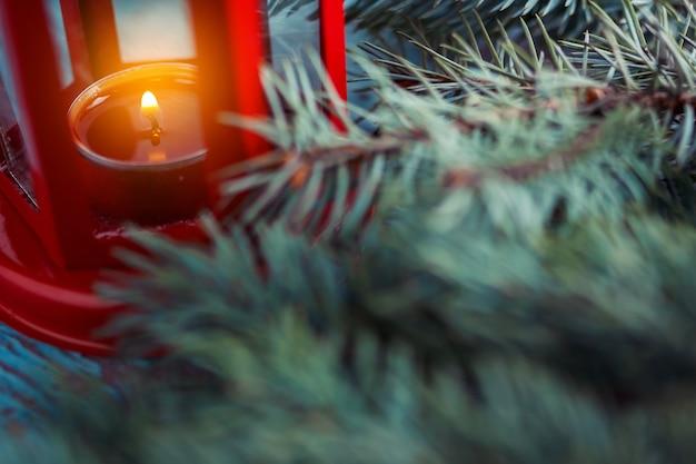 Alte rote laterne mit einer brennenden kerze nach innen und einem weihnachtsbaum
