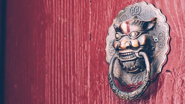Alte rote tür im chinesischen stil mit kupfernem löwenkopf-türknauf. traditionelle architekturdekoration zum schutz des bösen.