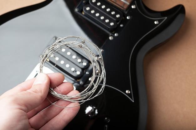 Alte saiten in der hand vor dem hintergrund des körpers einer gitarre ohne saiten.