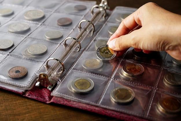 Alte sammlermünzen auf einem holztisch dunkler hintergrund banner numismatik münzen im album