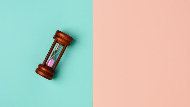 Alte sanduhr auf blauem und rosafarbenem hintergrund