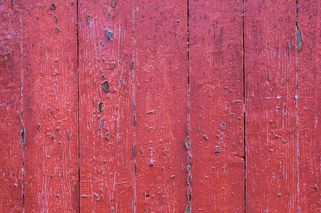 Alte schäbige hölzerne planken mit roter gebrochener farbfarbe als hintergrund
