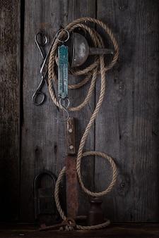 Alte scheren und seil, die an einer hölzernen wand hängen