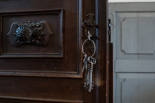 Alte schlüssel in einem schlüsselloch. alte rostige holztür mit schlüssel.
