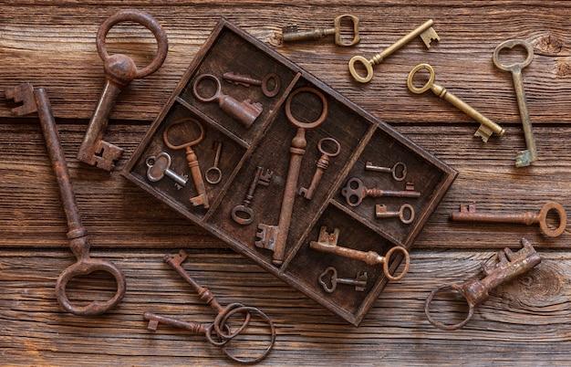Alte schlüssel in einer holzkiste auf einem hölzernen hintergrund der weinlese.
