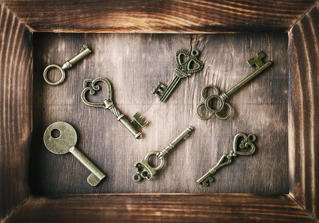 Alte schlüssel liegen auf einem holztisch.