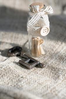 Alte schlüssel- und bildlaufnachricht in der flasche mit dem weißen sackleinenhintergrund. konzepthintergrund für valentinstag.