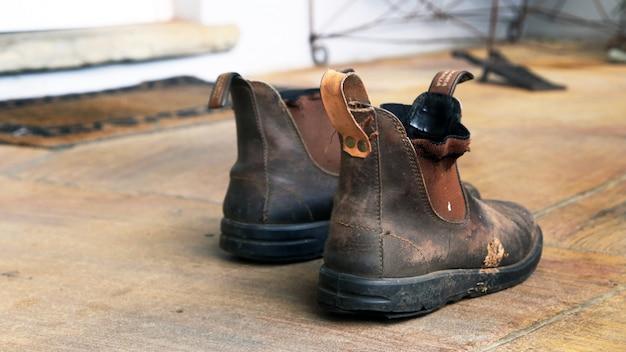 Alte schmutzige arbeitsstiefel im raum auf dem boden