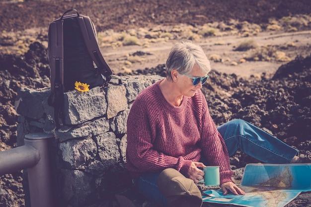 Alte schöne frau setzt sich während trekkingreisen mit rucksack und papierkarte im freien hin und genießt die natur und den alternativen urlaubslebensstil mit freiheit und gefühl mit dem weltweg world