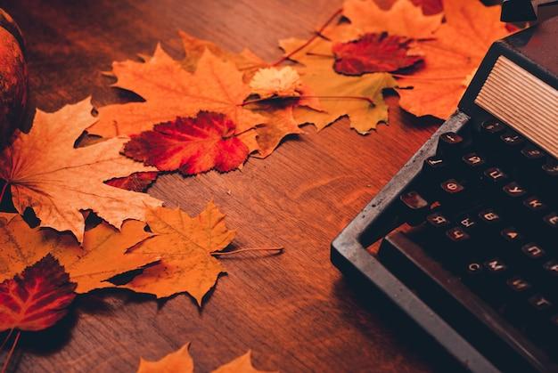 Alte schreibmaschine mit blättern. konzept herbst