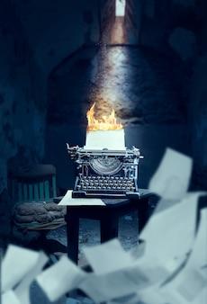 Alte schreibmaschine mit dem eingelegten brennenden blatt papier