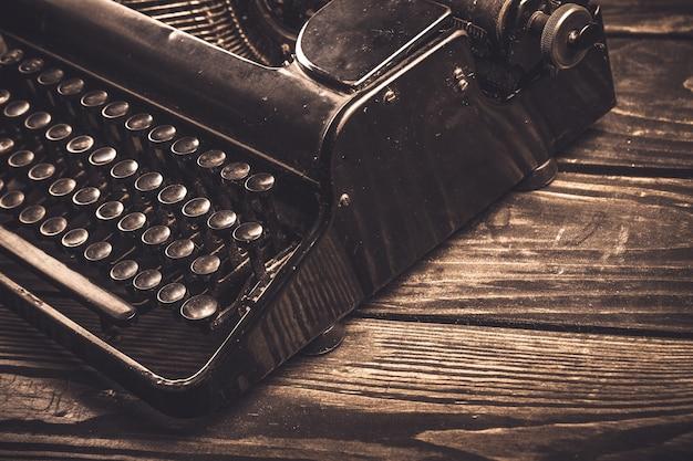 Alte schreibmaschine mit papier auf tischhintergrund