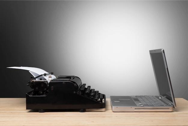 Alte schreibmaschine und laptop auf holztisch