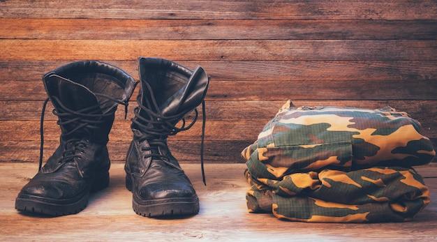 Alte schwarze herrenstiefel und militäruniform
