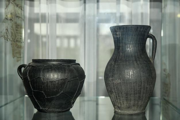 Alte schwarze keramikkrüge mit mustern.