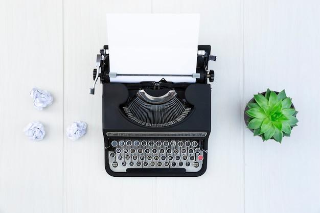 Alte schwarze schreibmaschine mit leerem blatt papier auf hellem holzschreibtisch