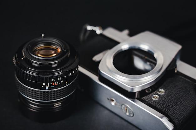 Alte slr-filmkamera und ein objektiv auf schwarzem hintergrund, fotografie-konzept.